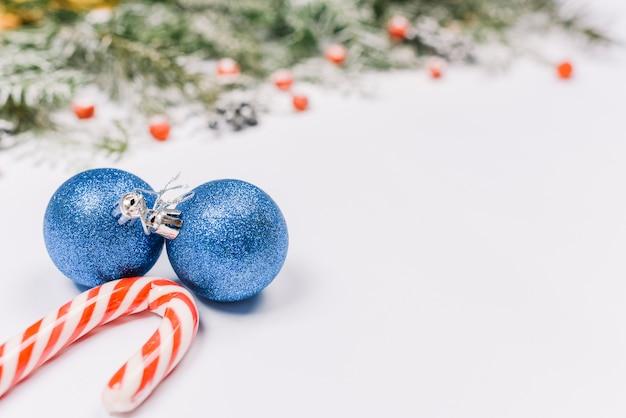 Boules bleues avec une canne en bonbon près des branches de sapin Photo gratuit