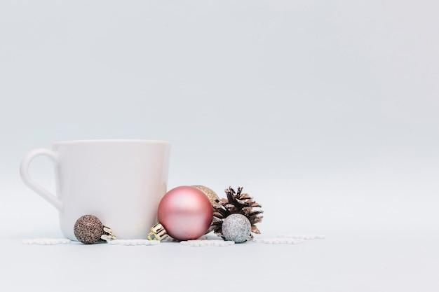 Boules brillantes avec tasse blanche Photo gratuit
