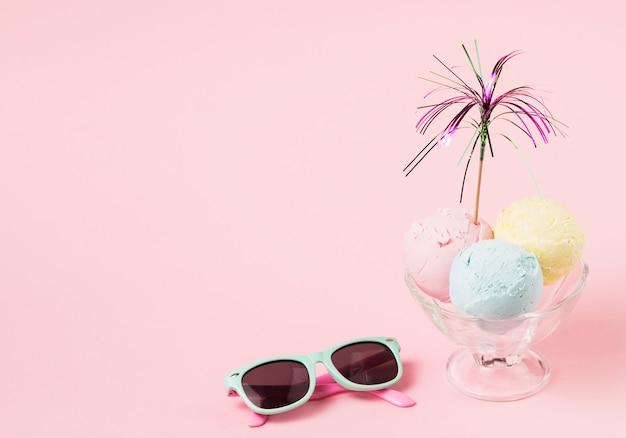 Boules de crème glacée avec baguette décorative sur un bol en verre près de lunettes de soleil Photo gratuit