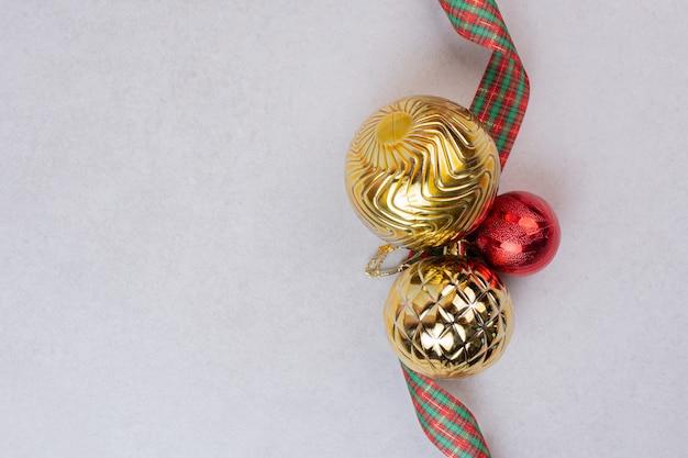 Boules De Décoration De Noël Avec Bande Sur Surface Blanche Photo gratuit
