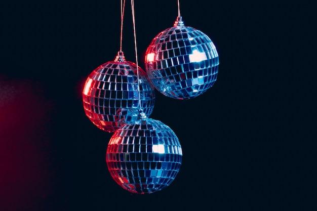 Boules disco étincelantes suspendues dans les airs sur fond noir Photo Premium