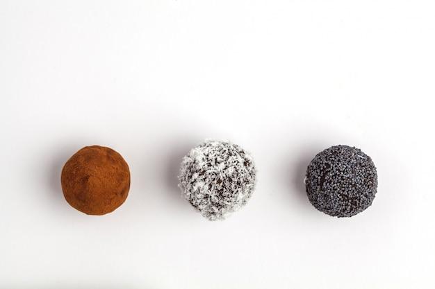 Boules d'énergie brute maison végétalien en bonne santé avec caroube, coquelicot et noix de coco, isolé sur fond blanc, vue de dessus Photo Premium