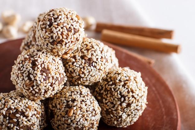 Boules d'énergie gâteaux aux amandes, sésame, noix de cajou, noix, dattes et blé germé, vue latérale, gros plan. Photo Premium