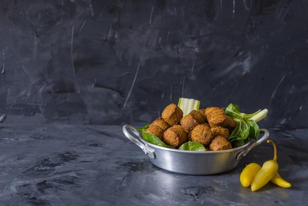 Boules de falafel servies en assiette avec green leafs sur fond noir en bois Photo Premium