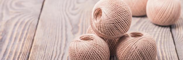 Boules de fil pour tricoter sur un fond en bois. Photo Premium