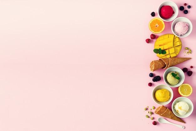 Boules de glace dans des bols, cornets de gaufres, baies, orange, mangue, pistache sur rose shabby chic. collection colorée, appartement plat, concept d'été, vue de dessus Photo Premium