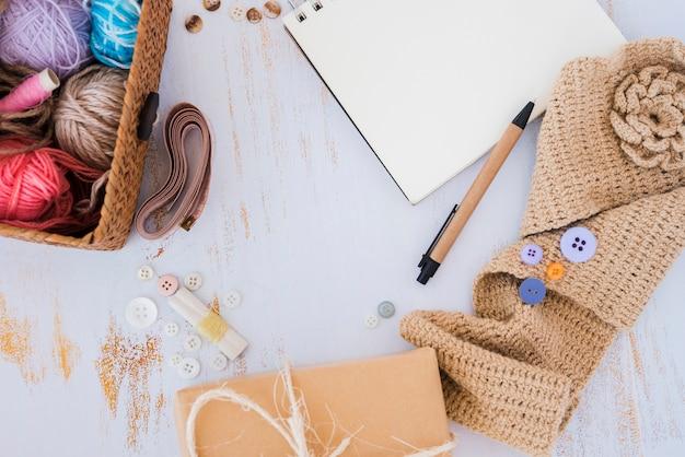 Boules de laine dans le panier; mètre ruban; bouton et crochet sur le bureau en bois Photo gratuit
