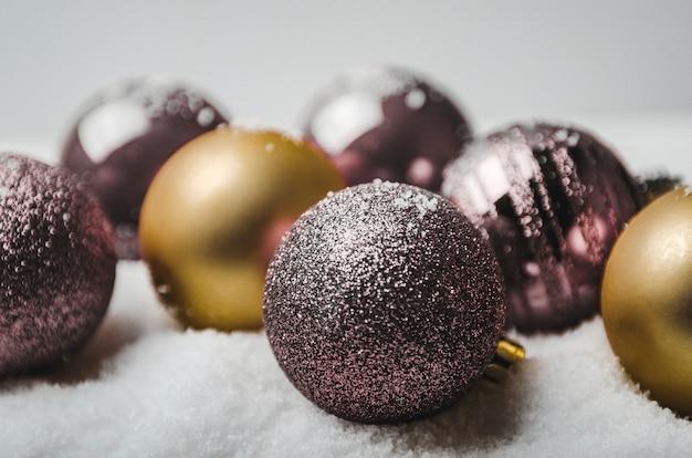Boules de noël boules de pourpre et d'or sur neige artificielle Photo Premium