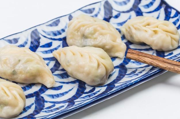 Boulette Bouillie Fraîche Sur La Plaque. Nourriture Chinoise Avec Des Vapeurs Chaudes Sur Le Fond. Photo Premium