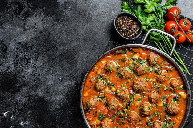 Boulettes De Boeuf Avec Sauce Tomate Et Légumes Dans Une Casserole. Fond Noir. Vue De Dessus. Espace Pour Le Texte Photo Premium