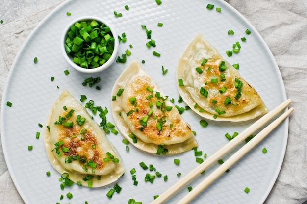 Boulettes frites coréennes, baguettes, oignons verts frais. Photo Premium