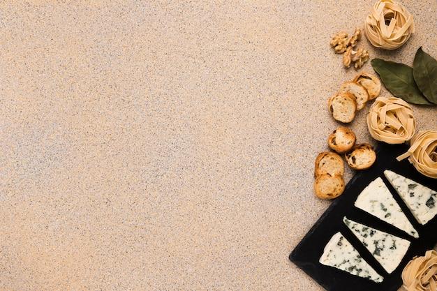 Boulettes de pâtes crues; tranches de pain; noyer et feuilles de laurier avec du gorgonzola sur l'ardoise à droite du fond Photo gratuit