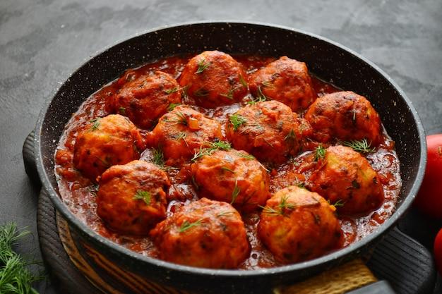 Boulettes De Poulet Appétissantes à La Sauce Tomate. Boulettes De Viande Dans Une Casserole Sur Une Table Sombre. Escalopes De Poulet à La Tomate. Plat De Viande. Photo Premium