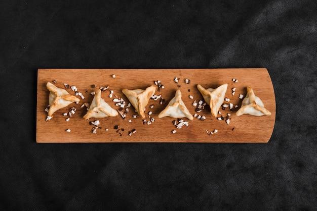 Boulettes triangulaires sur un plateau en bois sur le fond noir Photo gratuit