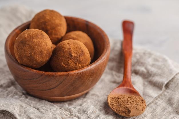 Boulettes de truffe raw energy végétaliennes saines avec caroube dans un bol en bois. concept de nourriture végétalienne saine. Photo Premium