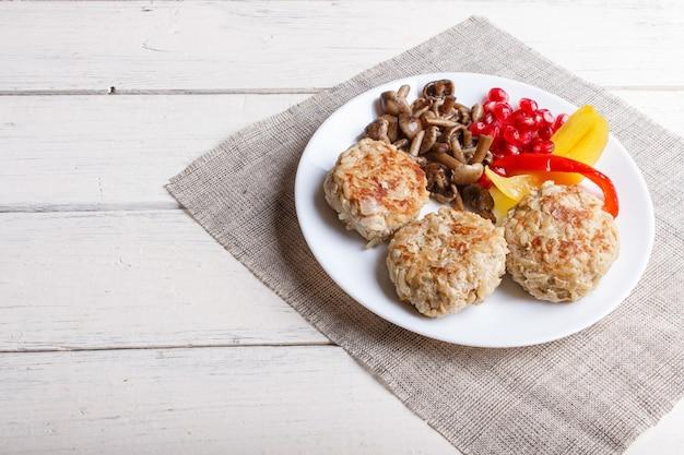 Boulettes de viande avec des champignons de riz, poivrons et graines de grenade sur bois blanc. Photo Premium