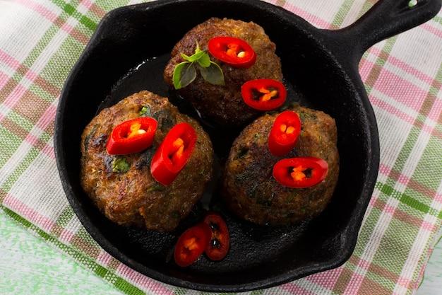 Boulettes de viande grillées avec des tranches de piment rouge Photo Premium
