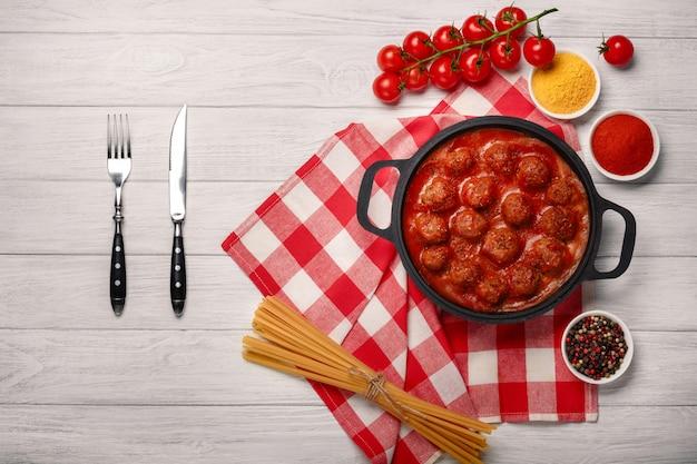 Boulettes de viande à la sauce tomate avec des épices dans une poêle à frire sur une planche de bois blanche Photo Premium