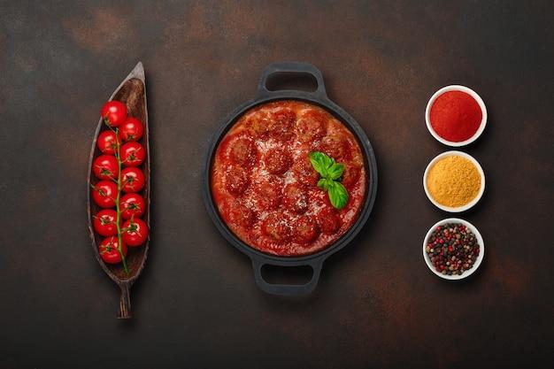Boulettes de viande à la sauce tomate avec épices, tomates cerises, paprika, curcuma et basilic dans une poêle à frire Photo Premium