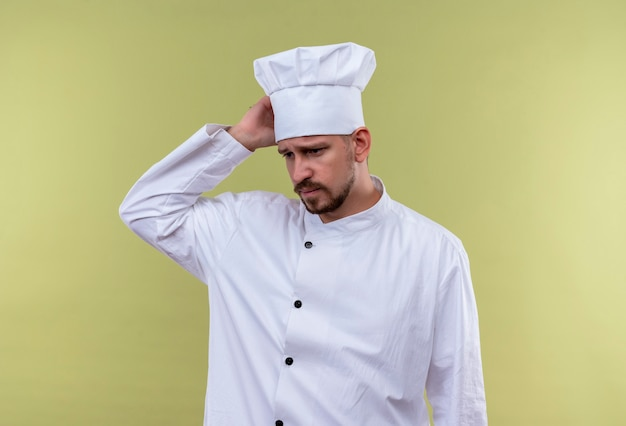 Bouleversé Chef Masculin Professionnel Cuisinier En Uniforme Blanc Et Chapeau De Cuisinier à La Fatigue Et Surmené Toucher Sa Tête Debout Sur Fond Gree Photo gratuit