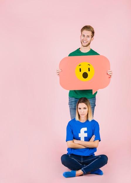 Bouleversé, femme, séance, devant, heureux, homme, tenue, choqué, emoji, bulle Photo gratuit