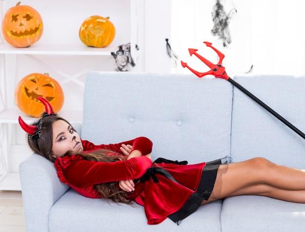 Bouleversé la jeune fille assise sur un canapé Photo gratuit