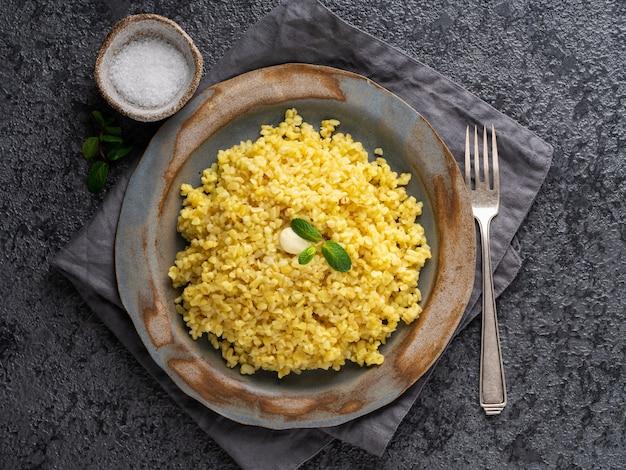Boulgour. bouillie de céréales bulghur dans une assiette sur une table en pierre gris foncé. nourriture végétarienne saine Photo Premium