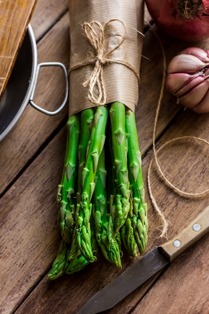 Bouquet d'asperges fraîches attachées avec de la ficelle, ustensiles de cuisine couteau à l'ail sur table en bois Photo Premium