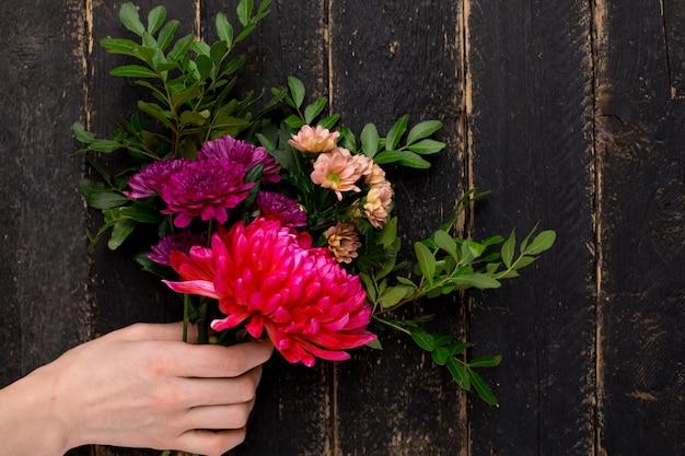 Bouquet de belles fleurs pour les vacances dans une main féminine sur bois Photo Premium