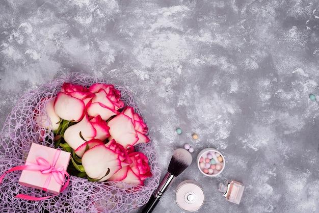 Bouquet de belles roses avec des cosmétiques sur béton gris Photo Premium