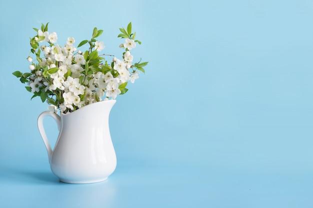 Bouquet De Branche De Cerisier En Vase Sur Fond Bleu. Photo Premium