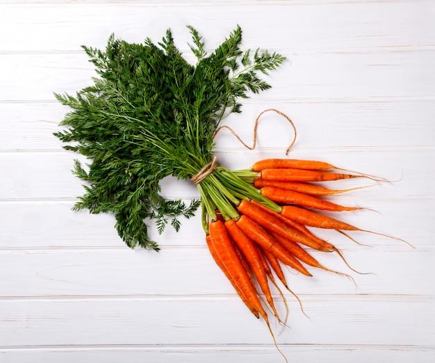 Bouquet de carottes fraîches avec des feuilles vertes sur fond blanc Photo Premium