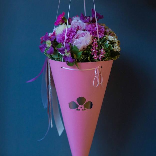 Un bouquet de carton rose de fleurs d'été saisonniers accroché sur un mur de studio Photo gratuit