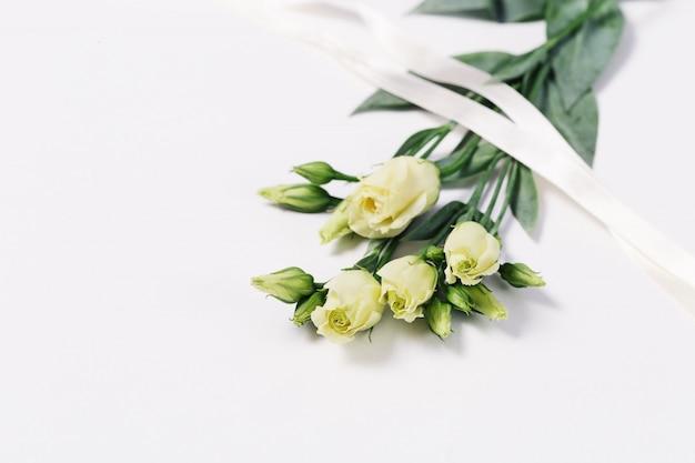 Bouquet D'eustoma Blanc Sur Fond Blanc Clair Avec Espace De Copie. Carte De Voeux Floral Pour Invitation Ou Félicitations. Photo Premium