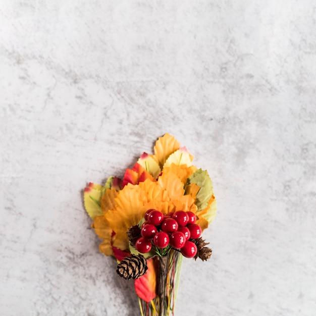 Bouquet de feuilles et de baies sur une surface minable Photo gratuit