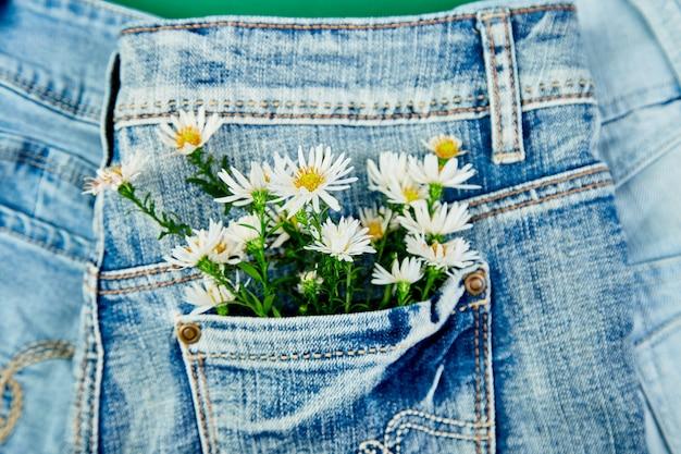 Bouquet de fleur blanche dans la poche d'un jean Photo Premium