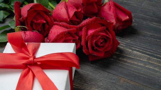 Bouquet de fleur rose rouge et blanc présente boîte sur une table en bois sombre. Photo Premium