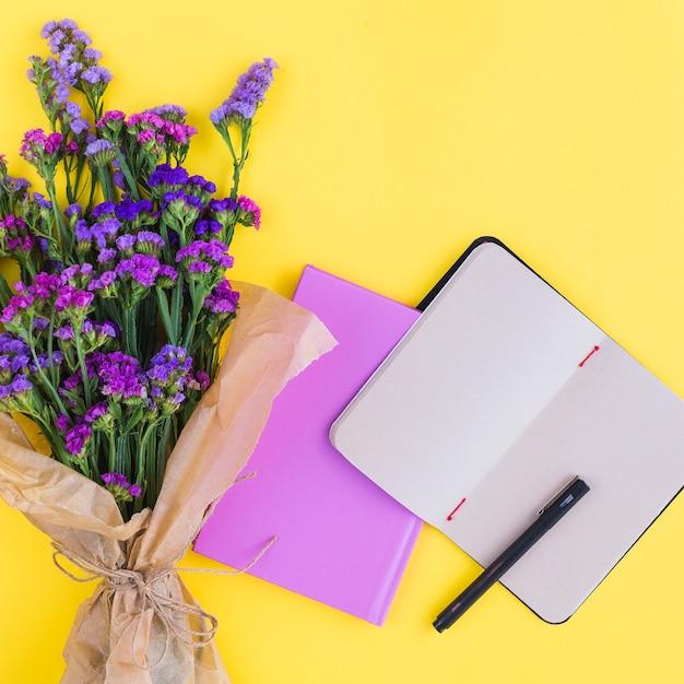 Bouquet De Fleurs; Agendas Et Stylo Sur Fond Jaune Photo gratuit