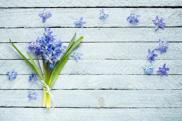Un bouquet de fleurs bleues sur un fond en bois Photo Premium
