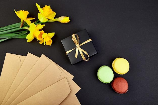 Bouquet de fleurs en cadeau narcisse et confiserie ou macarons en gâteau. Photo Premium