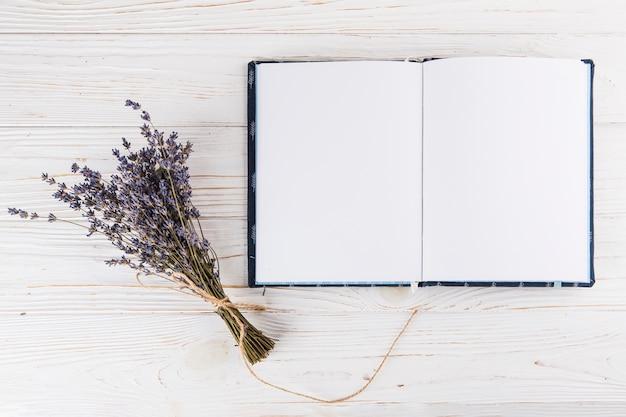 Bouquet de fleurs avec cahier vierge sur table lumineuse Photo gratuit