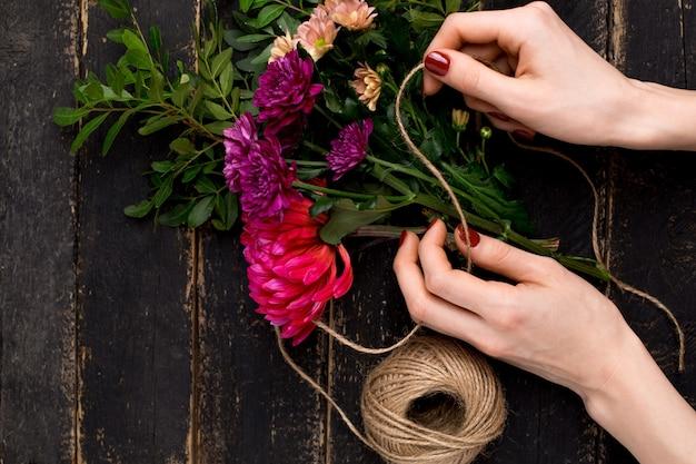 Bouquet de fleurs dans une main féminine sur une table en bois noire Photo Premium