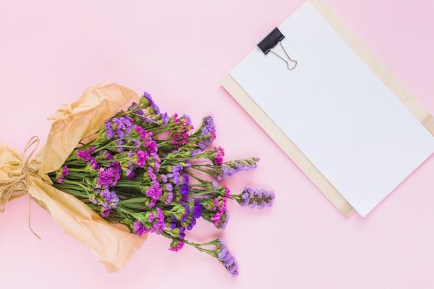 Bouquet de fleurs enveloppé dans du papier brun près du papier blanc vierge sur le presse-papiers Photo gratuit
