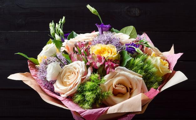 Un bouquet de fleurs sur un fond en bois sombre. bouquet de roses. Photo Premium