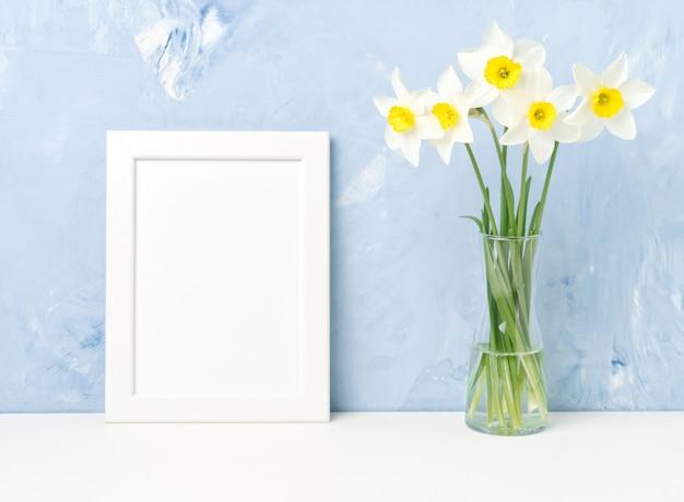 Bouquet de fleurs fraîches, cadre blanc sur table, en face du mur de béton texturé bleu. vide Photo Premium
