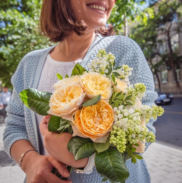 Bouquet de fleurs fraîches dans les mains de la fille Photo gratuit