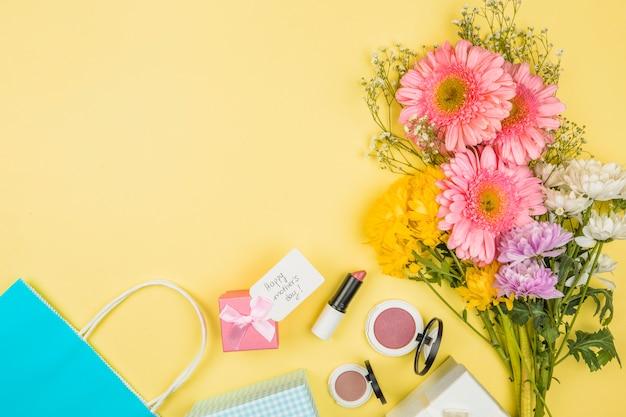 Bouquet de fleurs fraîches près de la balise avec des mots de joyeuses fêtes des mères sur la boîte de cadeau et des rouges à lèvres avec des poudres Photo gratuit