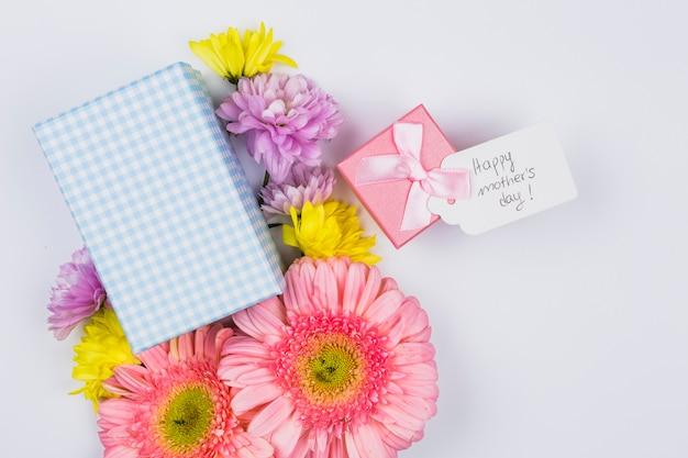 Bouquet De Fleurs Fraîches Près De Tag Avec Des Mots Et Des Boîtes à Cadeaux Photo gratuit