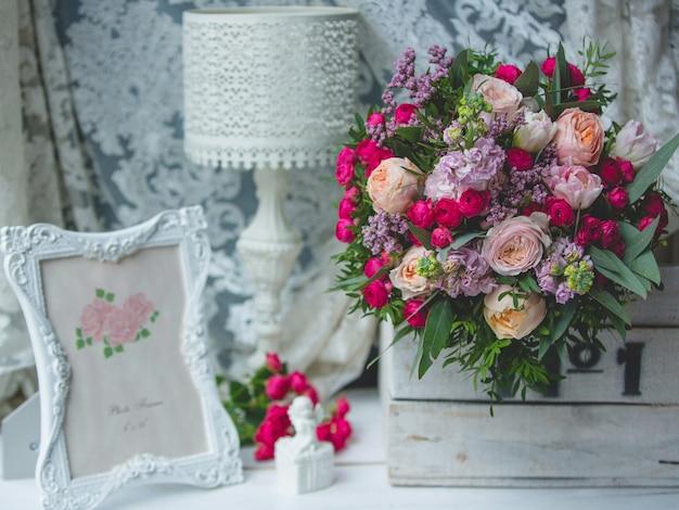 Bouquet de fleurs, lampe de lecture et cadre photo Photo gratuit