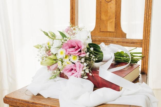 Bouquet De Fleurs Sur Le Livre Avec Foulard Sur Une Chaise En Bois Photo gratuit